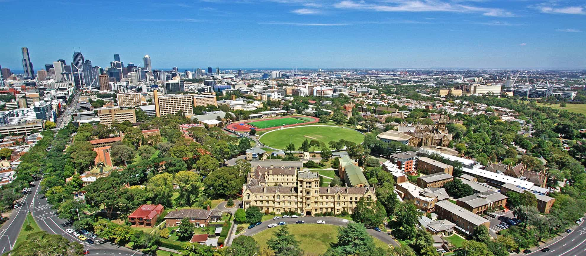 Aerial shot of the University of Melbourne campus - Queen's College in the foreground, and Melbourne CBD in the distance.